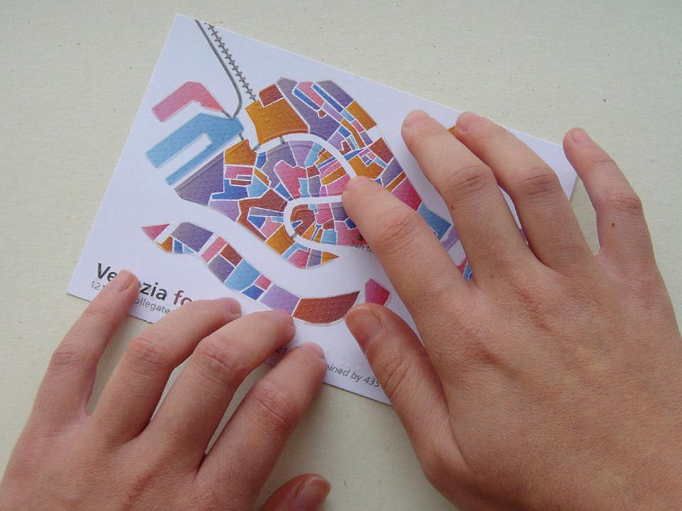 Mani che esplorano la cartolina tattile di Venezia forma urbis.