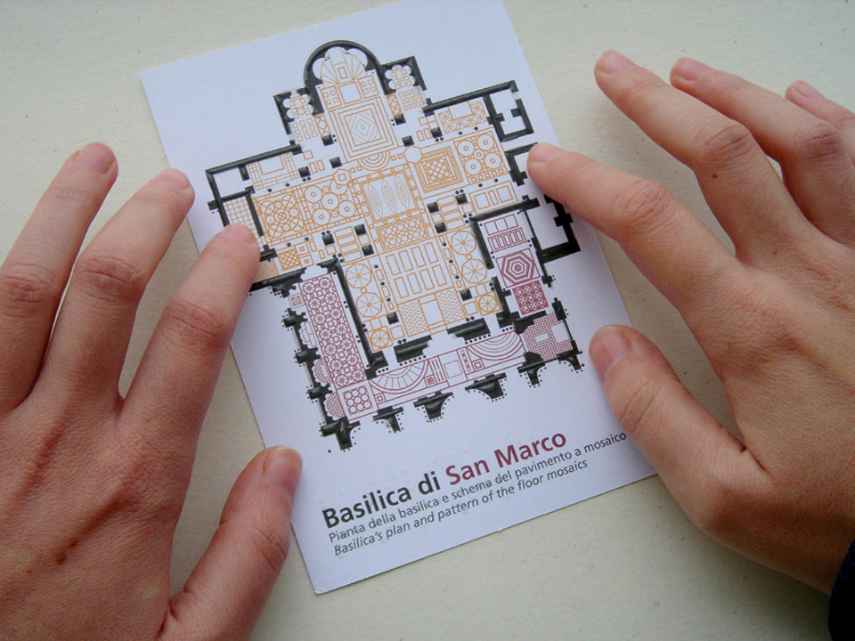 Mani che esplorano la cartolina tattile della Basilica di San Marco.